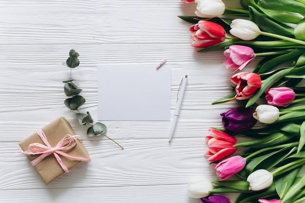 Concetto di giorno della madre bouquet di tulipani, regalo e carta con spazio di copia.