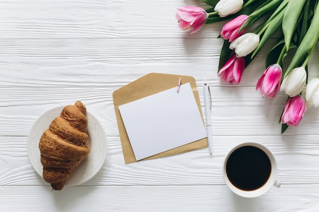 Concetto di giorno della madre bouquet di tulipani, cartoline, caffè e croissant.