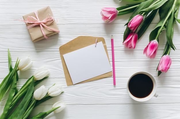 Concetto di giorno della madre bouquet di tulipani, cartoline, caffè e regali.