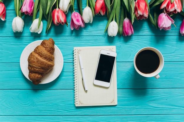 Concetto di giorno della madre tulipani, notebook, caffè, croissant e smartphone.