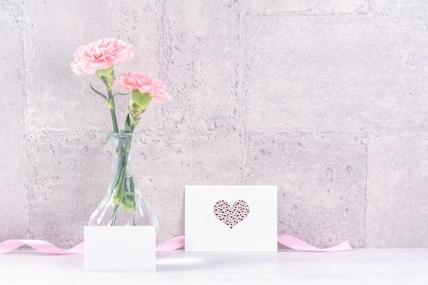 La sorpresa del giftbox fatto a mano per la festa della mamma augura la fotografia - bellissimi garofani in fiore con scatola di nastro rosa isolato su sfondo grigio design, close up, copia spazio, mock up