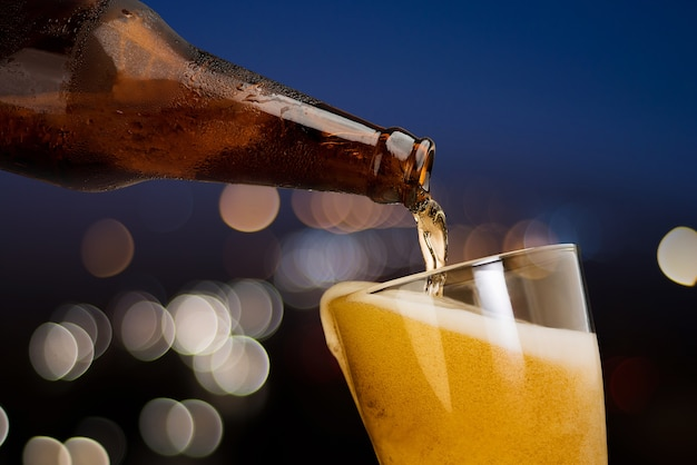 Moto di birra che versa dalla bottiglia in vetro sul bokeh notte sfondo chiaro