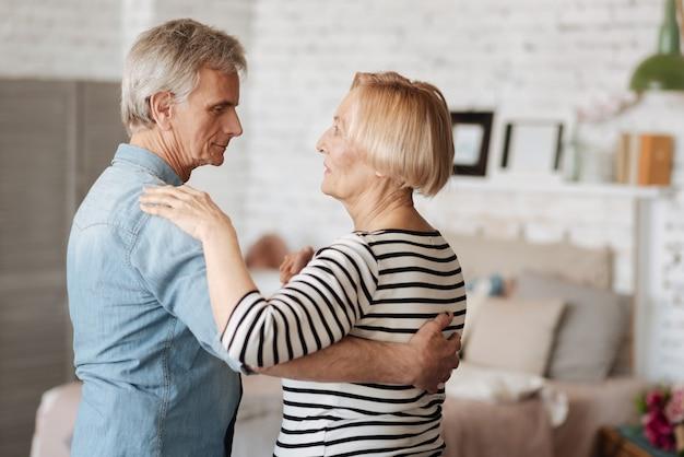 Movimento d'amore. coppia senior emotiva attiva condividendo un momento romantico mentre si gode il loro tempo e lo spendono a casa