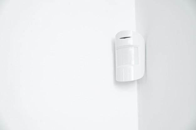 Sensore di movimento nell'angolo bianco. dispositivo che traccia il movimento degli oggetti. viene utilizzato per automatizzare il funzionamento di elettrodomestici, videocamere di sorveglianza, allarmi e sistemi di sicurezza