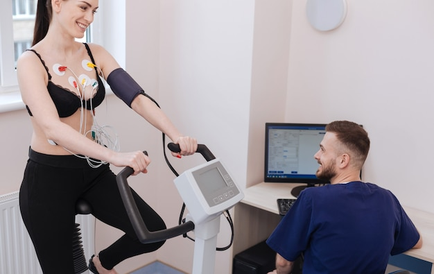Affascinante giovane donna motivata che si sente benissimo mentre fa alcuni esercizi e il medico esamina i risultati delle sue prestazioni