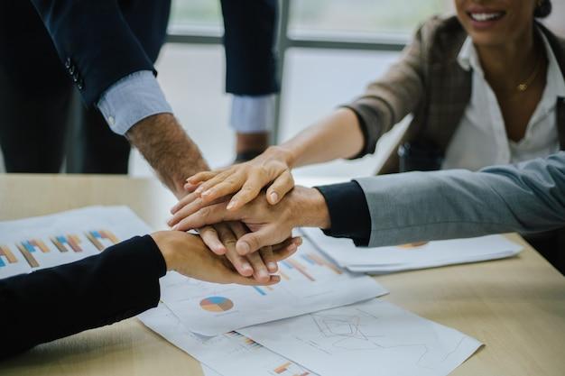 Team di affari multirazziale motivato ed eccitato che dà il cinque per celebrare la crescita aziendale e il successo finanziario