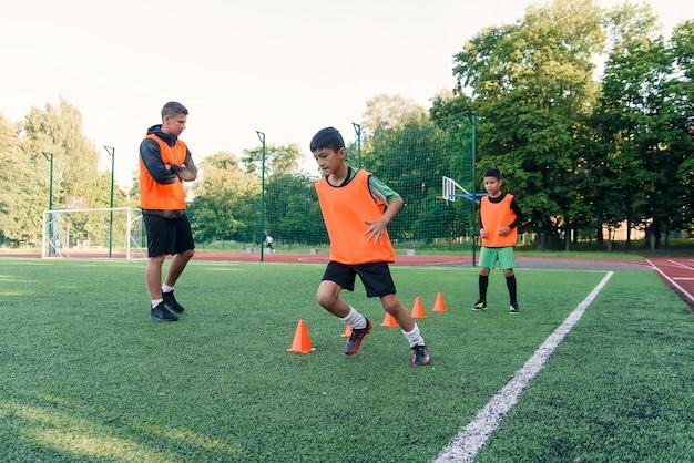 Ragazzi di 13 anni sportivi motivati con giubbotti arancioni che corrono tra i coni di plastica durante gli allenamenti di calcio allo stadio.