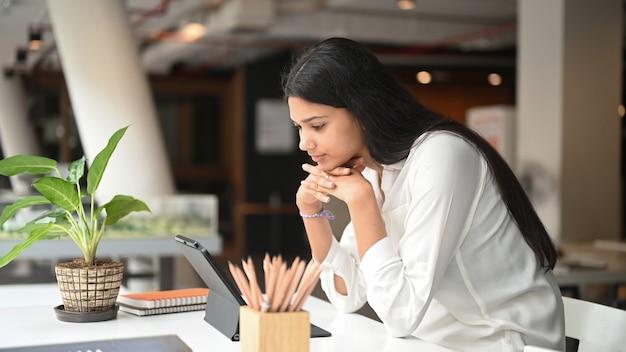 Motivato giovane imprenditrice piallatura la sua strategia con tablet sul tavolo bianco.
