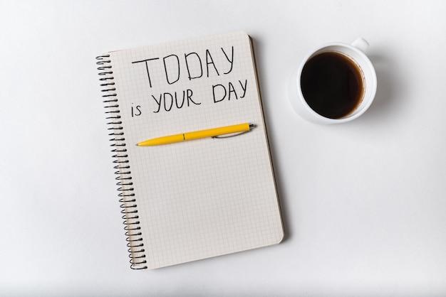 Iscrizione motivazionale nel blocco note oggi è il tuo giorno. caffè, quaderni e penna. grafia