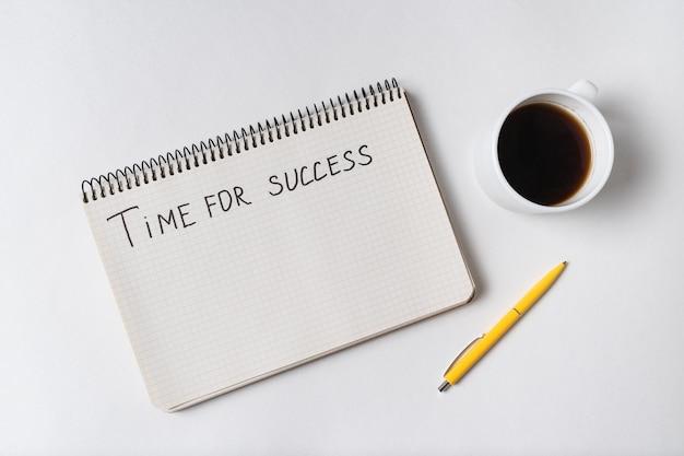 Iscrizione motivazionale tempo di successo. vista dall'alto di notebook, penna e tazza di caffè.