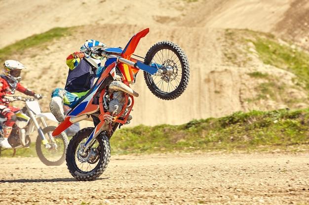 Pilota di motocross in azione che accelera la moto decolla e salta sul trampolino di lancio in pista