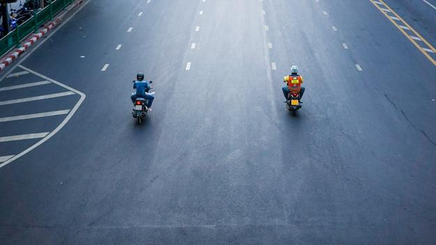 I motocycles stanno viaggiando sulla strada di città con il crosswalk firmano durante il giorno