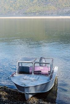 Barca a motore ormeggiata vicino alla riva del lago di montagna. russia, altai, lago teletskoye, capo kirsay