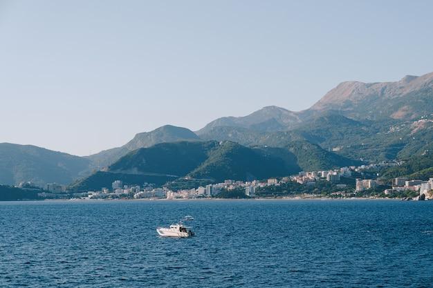 Imbarcazione a motore in mare contro la costa di budva e le montagne in montenegro
