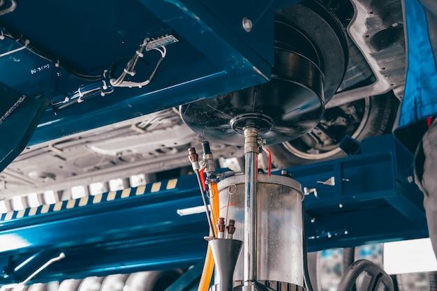 Contenitore dell'olio motore per il riempimento del vecchio olio motore dall'automobile in garage