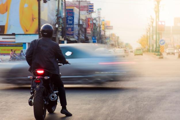 Una moto parcheggiata al semaforo e passa un'auto.
