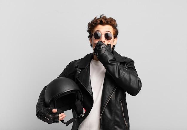 Ragazzo motociclista che copre la bocca con le mani con un'espressione scioccata e sorpresa, mantenendo un segreto o dicendo oops