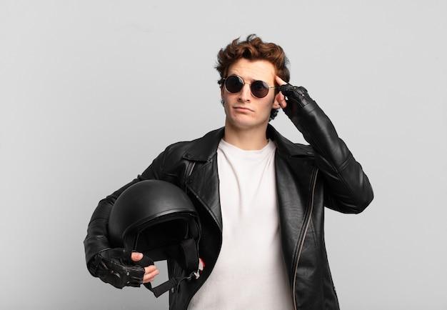 Ragazzo motociclista che si sente confuso e perplesso, mostrando che sei pazzo, pazzo o fuori di testa