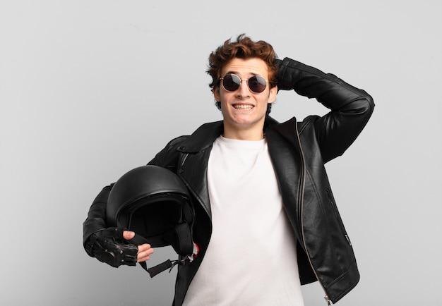 Ragazzo motociclista che si sente stressato, preoccupato, ansioso o spaventato, con le mani sulla testa, in preda al panico per l'errore
