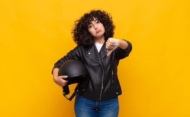 Motociclista donna che si sente arrabbiata, arrabbiata, infastidita, delusa o scontenta, che mostra i pollici verso il basso con uno sguardo serio