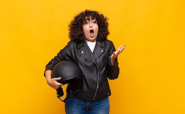 Motociclista donna che si sente estremamente scioccata e sorpresa, ansiosa e in preda al panico, con uno sguardo stressato e inorridito
