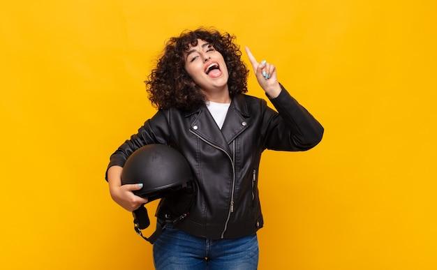 Donna motociclista che si sente come un genio felice ed eccitato dopo aver realizzato un'idea, alzando allegramente il dito, eureka!