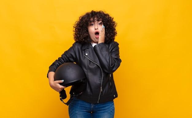 Donna del motociclista che si sente scioccata e spaventata, sembra terrorizzata con la bocca aperta e le mani sulle guance