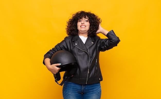 Motociclista donna che si sente stressata, preoccupata, ansiosa o spaventata, con le mani sulla testa, in preda al panico per errore