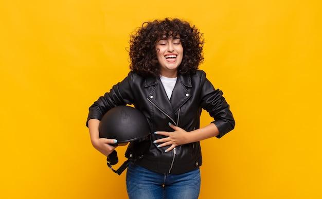 Motociclista donna che ride ad alta voce a uno scherzo esilarante, sentendosi felice e allegra, divertendosi