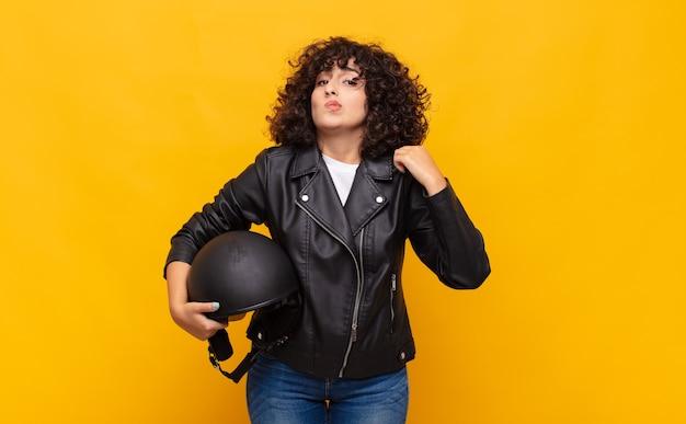 Donna del motociclista che sembra arrogante, di successo, positiva e orgogliosa, che punta a se stessa