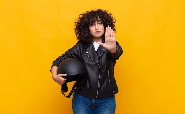 Donna del motociclista che sembra seria, severa, dispiaciuta e arrabbiata che mostra il palmo aperto che fa il gesto di arresto