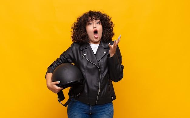 Motociclista donna a bocca aperta e stupita, scioccata e sbalordita da un'incredibile sorpresa