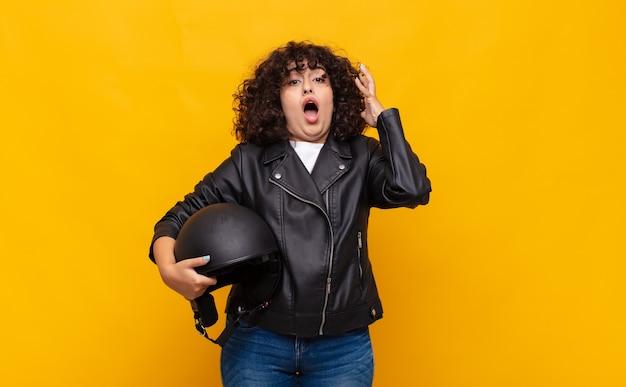 Donna del motociclista che urla con le mani in aria, sentendosi furiosa, frustrata, stressata e sconvolta