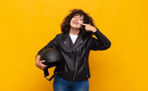 Donna del motociclista che sorride fiduciosamente indicando il proprio ampio sorriso, atteggiamento positivo, rilassato e soddisfatto
