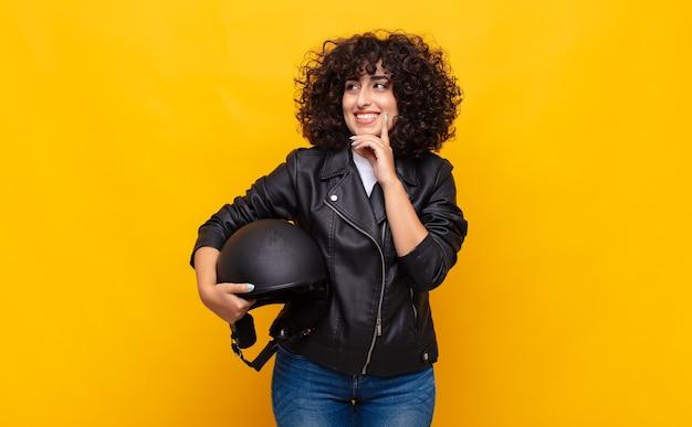 Motociclista donna sorridente felicemente e fantasticando o dubitando, guardando al lato