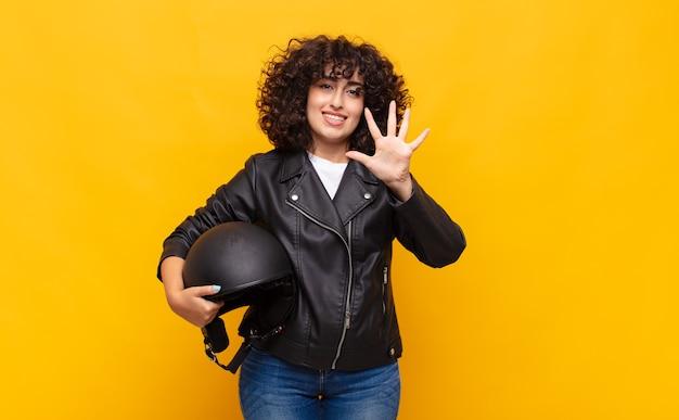 Motociclista donna sorridente e guardando amichevole, mostrando il numero cinque o quinto con la mano in avanti, il conto alla rovescia