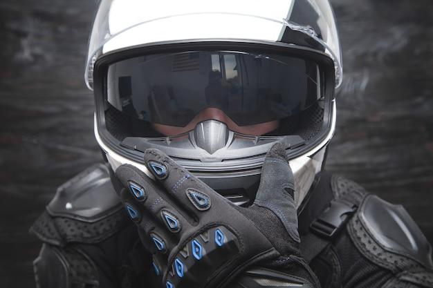 Motociclista che indossa un casco alla moda e guanti protettivi
