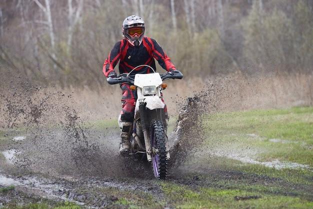 Ciclista di motocross che corre in una zona rurale mentre spruzza acqua sporca
