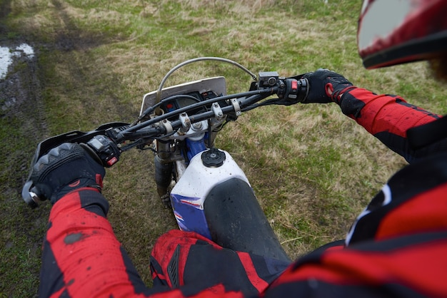 Pilota di motocross in movimento tenendo per le maniglie nere della sua moto