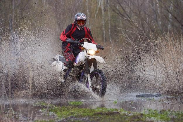 Pilota di motocross che corre in legno allagato lungo la strada con grandi pozzanghere