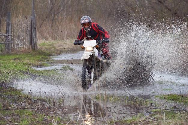 Pilota di motocross che corre in legno allagato durante il motocross in primavera