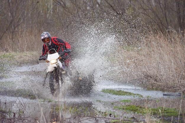 Pilota di motocross che corre in legno allagato in primavera