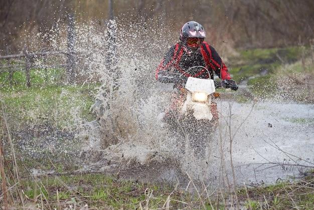 Pilota di motocross che corre in legno allagato mentre è seduto sulla sua moto durante il movimento