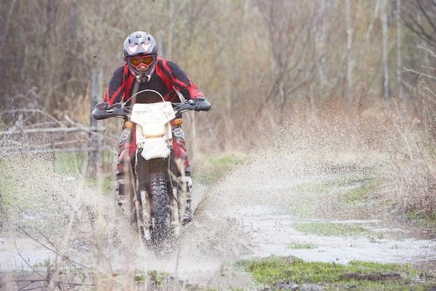Pilota di motocross che corre in legno allagato con schizzi sporchi tutt'intorno a lui