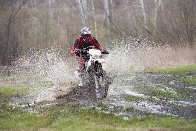 Pilota di motocross che corre in pista di fango durante la competizione all'aperto