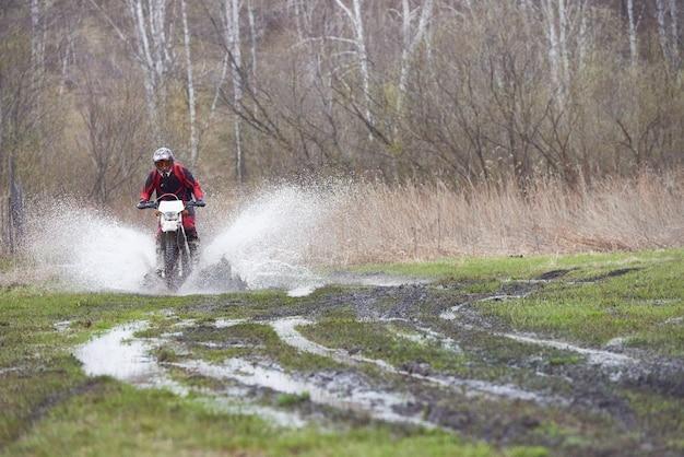 Pilota di motocross che corre su una pista di fango mentre si muove lungo la strada di campagna