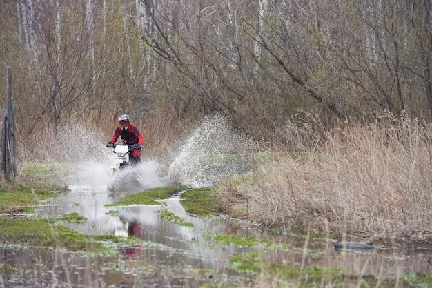 Pilota di motocross che corre nelle pozzanghere durante la competizione in ambiente naturale