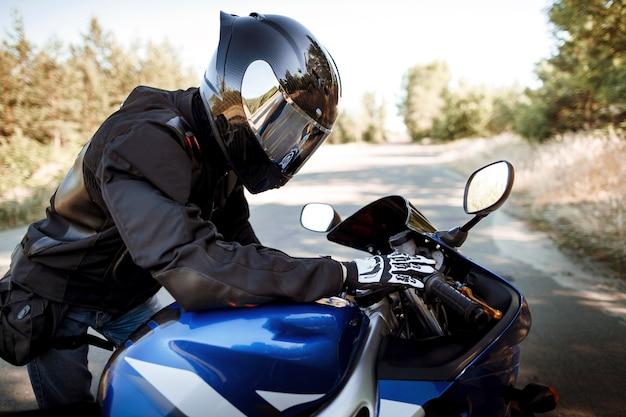 Motociclista in casco e giacca di pelle si siede su una moto sportiva sulla strada sullo sfondo della foresta. bellissimo sfondo, un posto per lo spazio della copia