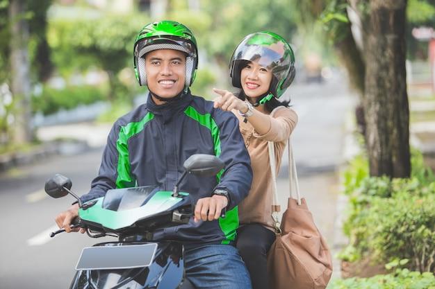 Tassista del motociclo che porta il suo passeggero a destinazione