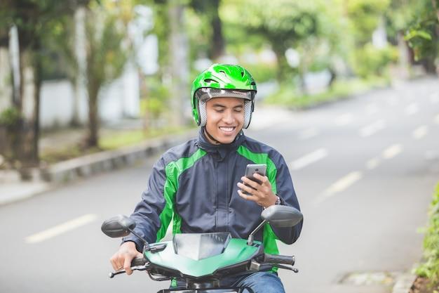 Tassista del motociclo che prende ordine tramite l'app online del telefono cellulare
